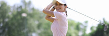 Female Golfer Smiles And Looks Along After Making Hit With Club. Women's Golf Concept