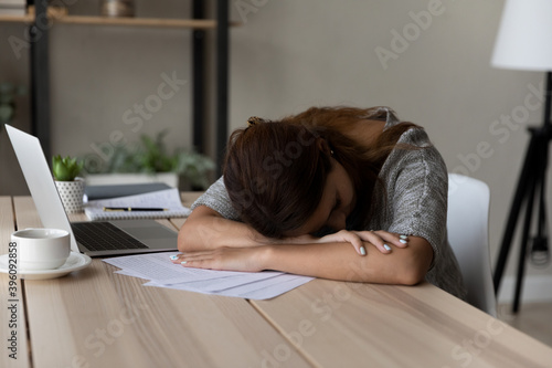 Fotomural Exhausted unmotivated young female worker fallen asleep at table working with paper documents, feeling lack of energy at workplace, sleepy woman tired of exam preparing or studying at home office