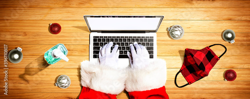 Santa Claus using a laptop computer with a mask and a sanitizer bottle from above