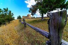 Campo Con Flores Blancas Y Amarillas, Cielo Azul Con Nubes Blancas En Día Soleado Y Castillo Medieval Al Fondo.
