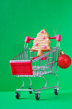 Shopping Cart With Gingerbread Christmas Tree And Red Bauble Against The Green Background. Shopping For New Year Presents