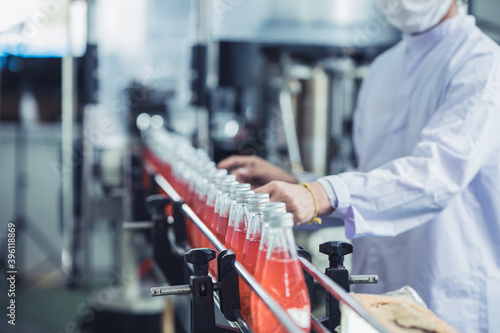 Fotografia Drink factory - closeup hygiene worker working check juice glass bottled in prod