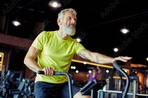 Obraz Exercises after 50. Side view of a mature athletic man in sportswear doing cycling on exercise bikes at gym - fototapety do salonu