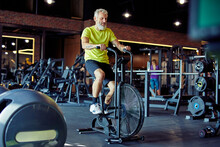 Cardio Workout. Full Length Of A Mature Athletic Man In Sportswear Doing Cycling On Exercise Bikes At Gym