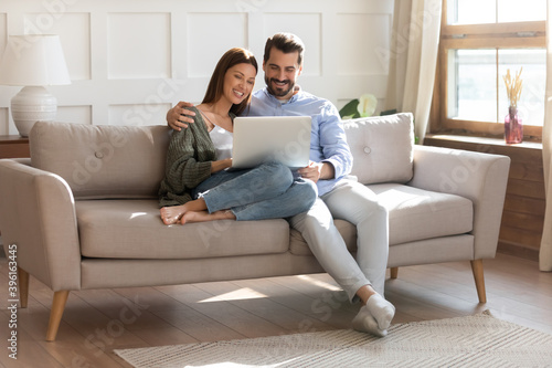 Fotomural Happy young Caucasian couple renters relax on sofa in living room watch video on laptop together
