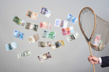 Hand Holding Butterfly Net With Flying Banknotes