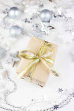 In The Center Of The Assorted Christmas Toys, There Is A Golden Gift Box Created From Kraft Paper On A White Background.