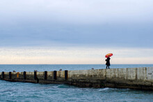 A Woman With A Bright Umbrella Walks On The Pier By The Sea