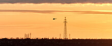 Power Transmission Lines And The Silhouette Of A Flying Helicopter Against The Background Of A Yellow-orange Multicolored Sunset