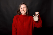 Cheerful Young Female In Red Knitted Sweater Demonstrating Alarm Clock Showing Almost Midnight Time While Standing Against Black Background