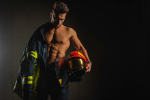 Young Handsome Adult, Muscular Firefighter In Uniform Holding Ax Of Fire Equipment In His Hands, Pensive, Isolated On Dark Background. Low Key. Protection Concept. There Is A Place For An Inscription