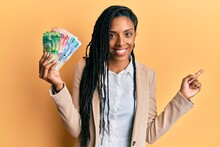 African American Woman Holding South African Rand Banknotes Smiling Happy Pointing With Hand And Finger To The Side