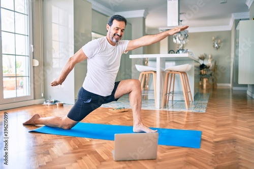 Fototapeta Middle age man with beard training and stretching doing exercise at home looking at yoga video on computer obraz