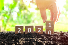 Male Hand Burying Year 2020 To Change To 2021 In Wooden Blocks Cubes. New Year, Hello And Goodbye Concept.