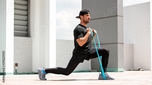 Obraz na plátne Handsome Latino sports man doing lunge workout with resitance band outdoors in t