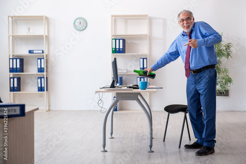 Fototapety, obrazy: Old male employee drinking alcohol in the office