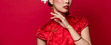 Asian Woman In Traditonal Chinese Cheongsam Dress Touching Her Face In Isolated Red Banner Background