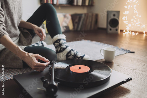 Young woman listening to music, relaxing, enjoying life at home. Girl wearing warm winter clothes having fun. Turntable playing vinyl LP record. Leisure, music, hobby, lockdown, lyfestyle concept