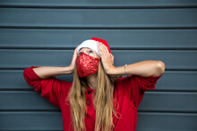 Longhair Blond Caucasian Girl In Red Christmas Hat, Hoodie And Sparkling Protective Mask Holds Head, Looks Up. I Do Not Know What To Do Gesture. Afraid Of Covid New Year. Grey Metal Wall Behind. Copy