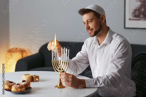 Photo Man lighting candles for Hannukah at home