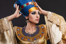Closeup Studio Portrait Of A Beautiful Woman With Brown Eyes And Evening Make-up In The Image Of Queen Cleopatra, Crown, Necklace, Golden Dress