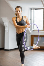 Athletic Woman Practising Rhythmic Gymnastics With A Hoop In The Gym