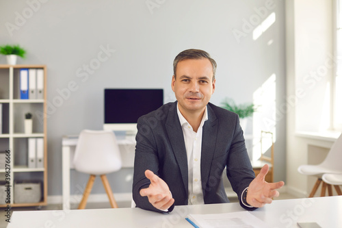 Foto Portrait of happy businessman sitting at desk in office, looking at camera and t