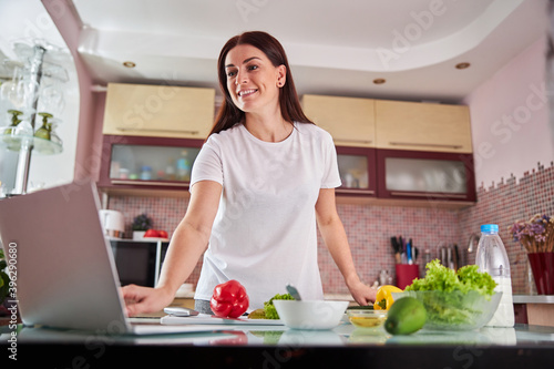 Photo Female clicking on a laptop standing among the ingredients