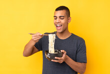Young African American Man Over Isolated Yellow Background Holding A Bowl Of Noodles With Chopsticks And Eating It