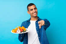 Young Handsome Man Holding Waffles Over Isolated Blue Background Points Finger At You With A Confident Expression