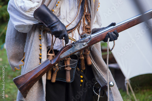 Photo Musketeer preparing to fire muskets at reenactment festival