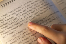 A Person Leads A Finger On The Lines In The Book, But Instead Of Letters Only Question Marks On The Page In The Textbook.
