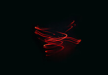 Red Glowing Spiral Of Red Color On A Black Background. Creative Texture, Smooth Lines Swirl, Movement On Dark Backdrop. Long Exposure Mixed Light Shooting. Creative Futuristic Desktop Wallpaper
