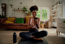 Portrait Of Smiling Young African Woman Using Smartphone After Routine Wokout With Bottle Besides At Home