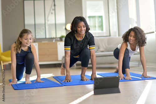 Young woman with kids doing fitness exercices at home, online class Fototapet