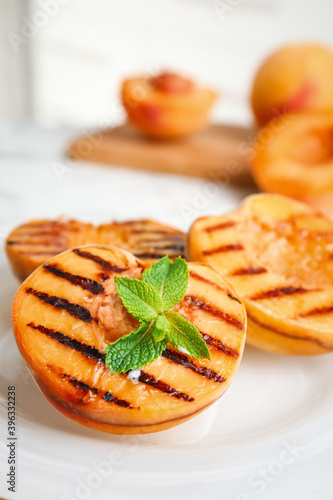 Delicious grilled peaches with mint on plate, closeup Fototapeta