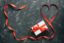 Valentine's Day. Gift And Heart From A Red Ribbon On A Black Stone Background. Top View, Flat Lay.