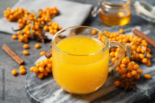 Fotografía Delicious sea buckthorn tea and fresh berries on grey table, closeup