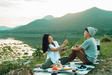 An Asian Girl's Artist Using The Pencil Is Skating, Painting A Portrait Of A Man Smiling Happily, Both Sitting On A Carpet. Funny Couple With Mountain View And Outdoor Reservoir In The Morning