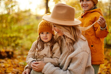 Mother With Kids In Autumn Nature, Adorable Lovely Female In Coat Enjoying Time With Little Children In The Autumn Forest, Smile