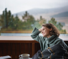 Young Happy Woman In Green Sweater By The Window In A Country House Chalet With A View Of The Mountains Chalet