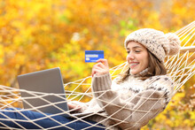 Happy Woman Buying Online On Hammock In Autumn Holiday