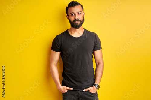 Fotografia arabic man with hands in pocket looks at camera, friendly guy posing, isolated y