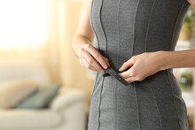 Woman Hands Fastening Belt Of Dress At Home