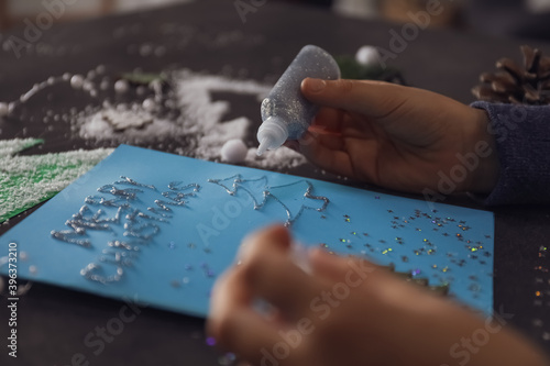 Little child making Christmas card at table, closeup