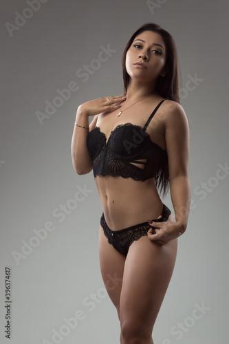 Fototapeta beautiful slim woman with black hair body and makeup standing, wears lace lingerie, lace bra and panties, studio obraz na płótnie