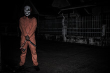 Asian Handsome Man Wear Clown Mask With Weapon At The Night Scene,Halloween Festival Concept,Horror Scary Photo Of A Killer In Orange Cloth