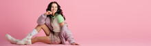 Side View Of Happy Young Woman In Stylish Winter Outfit Posing On Floor On Pink Background, Banner