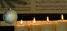 Christmas Decoration With Four Burning Candles, Spruce Branch, Piano And Music Paper