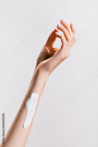cropped view of woman with hand cream on arm isolated on grey, stock image